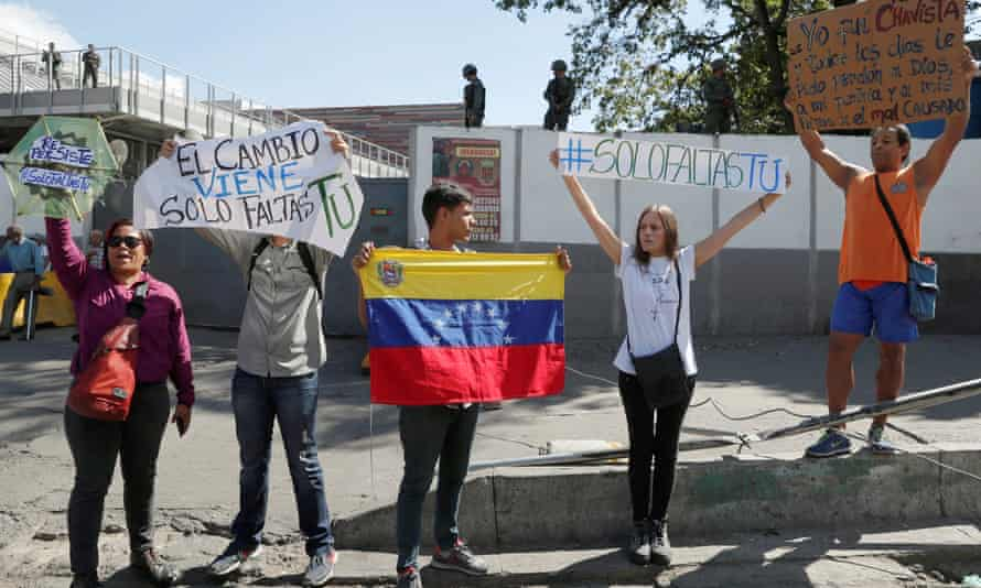 Supporters of Juan Guaidó demonstrate outside a military outpost in Caracas, Venezuela, on 27 January.