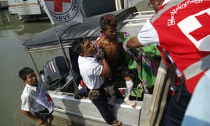 A Myanmar Red Cross worker helping a wounded boy off a boat on 23 March