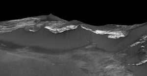 The image shows dark narrow streaks flowing down the west facing slopes of Coprates Chasma in the equatorial region of Mars.