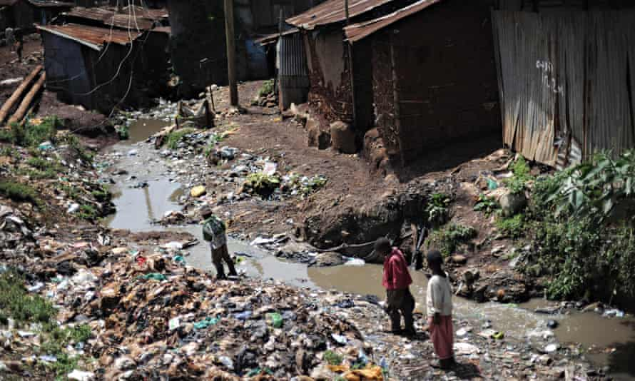 Three young residents of the second largest slum in African, Kibera, walk on the garbage-strewn basin of a water canal that makes its way through the slum on March 21, 2010.