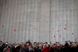 People watch as red paper poppies fall from the roof at the Menin Gate during a ceremony