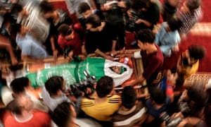 Palestinian mourners surround the body of Yazan al-Tubasi, killed during clashes in Gaza the previous day, during his funeral in Gaza City