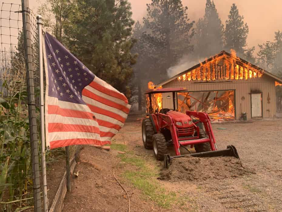 A red tractor is left behind as a home burns in Plumas county, California, impacted by the Dixie fire.
