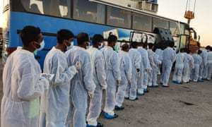 Migrants wearing overalls and face masks are lining up to board a bus after they disembarked from the Mare Ionio vessel in Pozzallo, southern Sicily on 20 June, 2020.