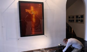 A cameraman films broken glass from Piss Christ, a controversial piece of art by Andres Serrano, after its partial destruction by two Catholic activists.