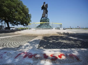 The word 'racism' is painted next to a statue memorializing the Confederacy with its tarp-covered base that was spray-painted with 'black lives matter' in Charleston, South Carolina
