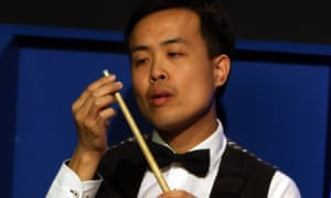 Marco Fu inspects his cue after the tip fell off during his semi-final against Mark Selby at the World Championship at the Crucible.