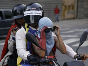 Caracas, Venezuela: Anti-government protesters ride alongside a march honouring people killed during months of deadly demonstrations against President Nicolas Maduro