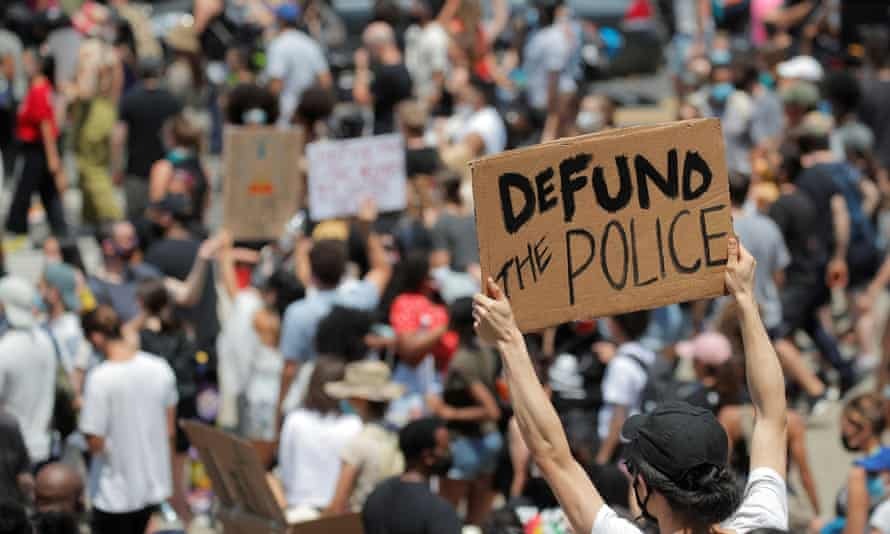 A demonstrator holds a sign reading 'Defund the Police' in New York.