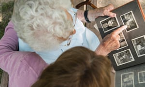 Senior woman sitting on park bench with granddaughter, looking at old photograph album