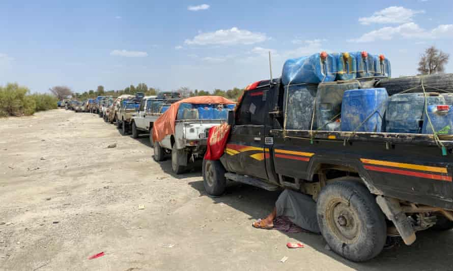 A driver rests under his pick-up truck to escape the scorching sun as petrol carriers queue to cross the border.