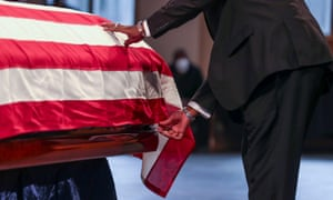 A man adjust the American flag on the casket of late Senator and Civil Rights leader John Lewis at the State Capitol in Atlanta on Thursday, the day of his funeral.