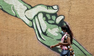 An Indian woman wearing a face mask walks past a mural in Bangalore coronavirus