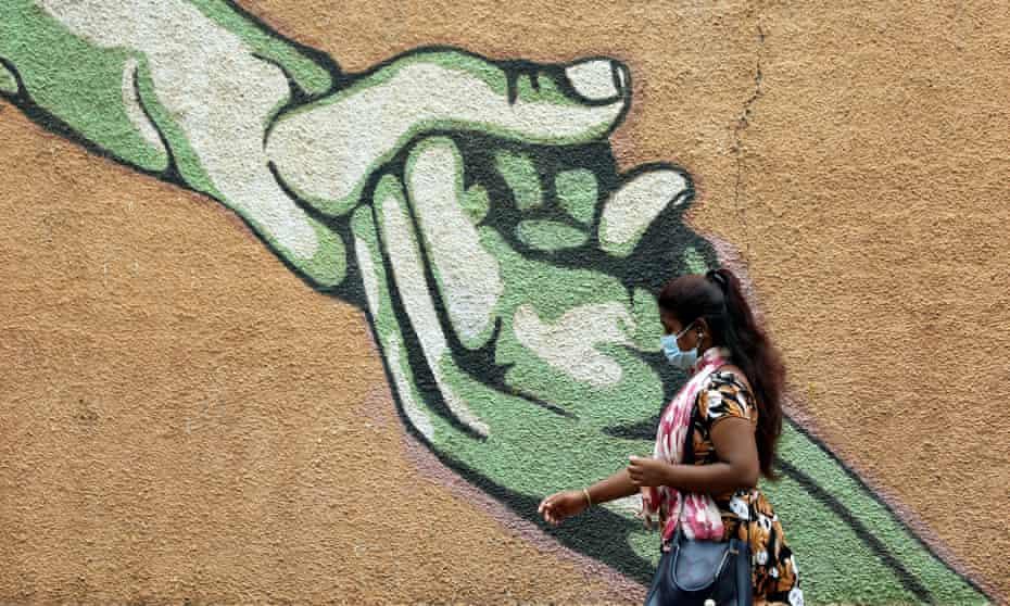 An Indian woman wearing a face mask walks past a mural in Bangalore coronavirus