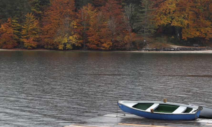 Rowing boats lie at Walchensee Lake near autumnal colored trees in Walchensee near Garmisch-Partenkirchen, Germany.