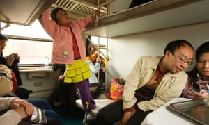 People traveling in a sleeper compartment of a train, China.