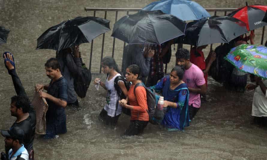 People walk along a flooded street in Mumbai