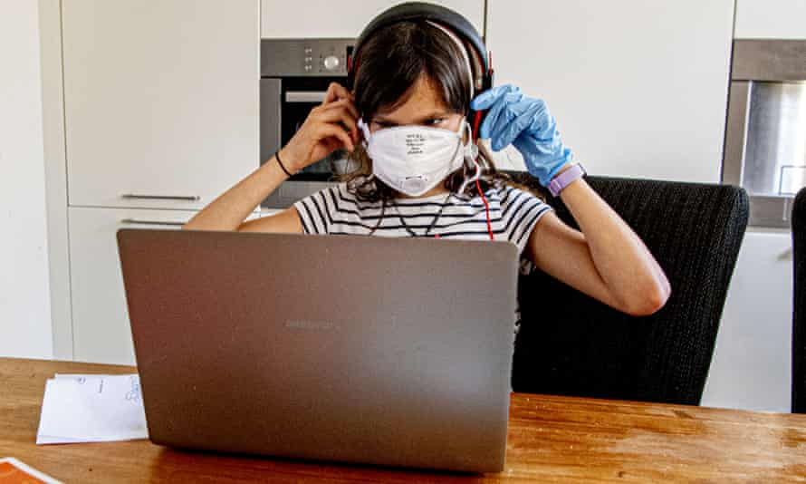 girl in face mask at laptop