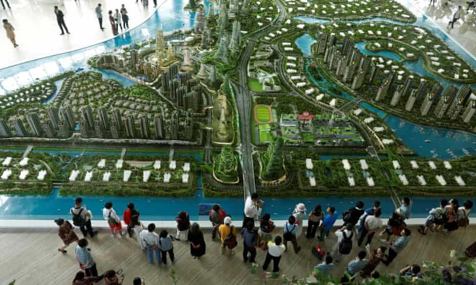 Prospective buyers look at a model of Forest City – a 'new Singapore' taking shape over the Johor Strait from the original.