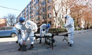 Workers wearing protective suits prepare a drone to spray disinfectant at a residential community in Shijiazhuang, China