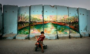 An Iraqi child sits in front of a painted 'security wall' in Baghdad, Iraq.