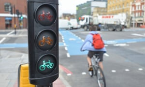 A cyclist passes traffic lights on a main road.