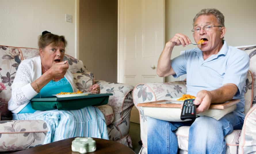 Couple sitting on sofa eating
