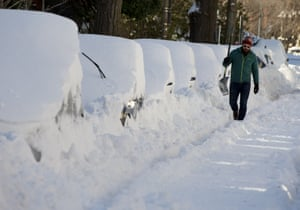 Ben Osborn walks with past a line of snowed-in cars