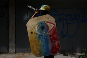 A demonstrator in Caracas holds  a shield and a knife