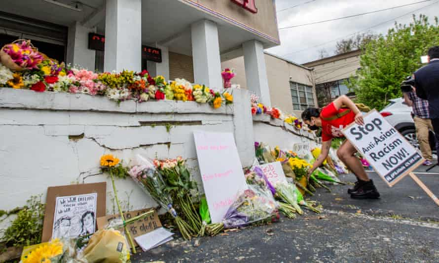 A woman holding a placard that reads 'Stop Anti-Asian Racism Now!' lays flowers at one of the Atlanta spas that saw the murder of eight people, six of them women of Asian descent.