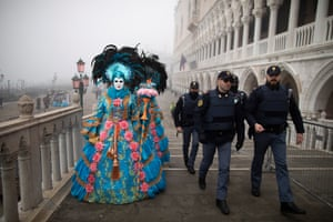 Police walk alongside costumed people near San Marco square during the Venice carnival
