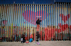 People paint hearts on the border wall at Baja California, Mexico