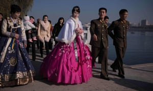 A bride and groom walk along the Taedong river