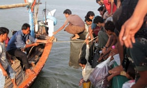 Indonesian fishermen (left) help transfer Rohingya migrants from their boat near the city of Geulumpang on 20 May as hundreds of starving asylum seekers were rescued the same day.