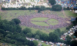 People form a giant peace sign at Glastonbury.