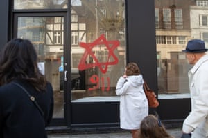Anti-semitic graffiti in the form of numbers, 9 11, and a Star of David, on a shop window in Belsize Park.