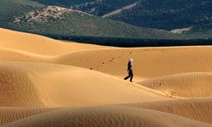 Sand dunes and figure walking across the Maowusu desert.