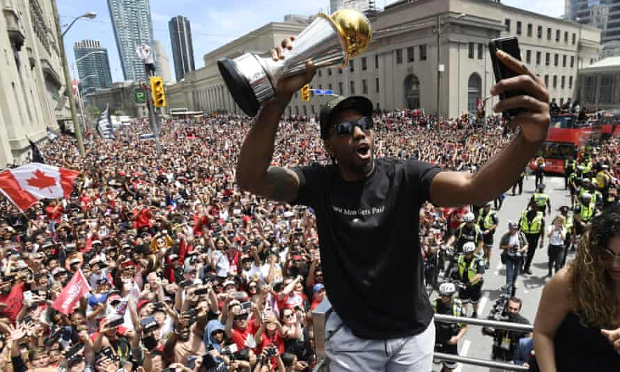 Kawhi Leonard takes a selfie in front of the crowd in Toronto