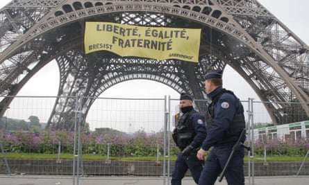 Police officers walk past the Eiffel tower, which sports the banner placed by Greenpeace activists.