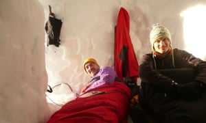 two men in sleeping bags on snow-holing holiday