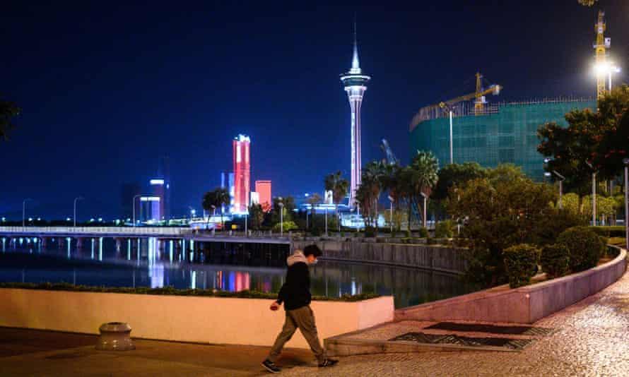 A man walks along the waterfront in Macau