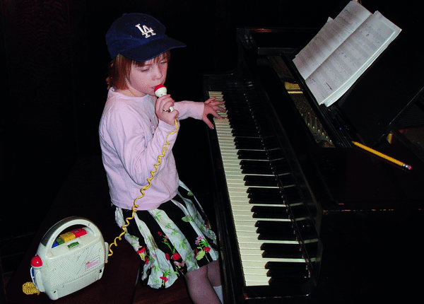 Billie Eilish sitting at a piano as a child