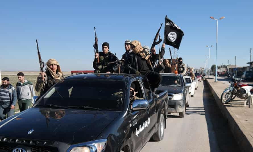 Islamic State militants pass through the Syrian border town Tel Abyad.
