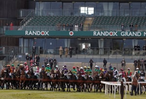 The runners in the Grand National line up for the start in front of empty stands except for a few owners.