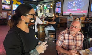 Restaurant owner Sandy Drown talks with a customer, Tim Schmidt, at the Happy Viking Sports Pub.