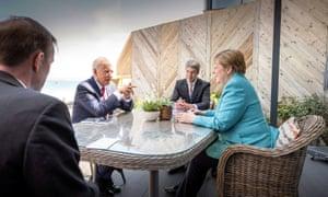 Joe Biden, Angela Merkel and advisers Jan Hecker and Jake Sullivan at an outdoor table.