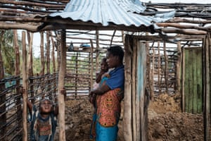 Ines Isaias takes shelter from the rain with her children at her home, which was destroyed by cyclone Idai in Beira