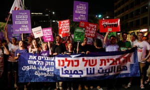 Israelis hold placards reading 'This house belongs to all of us' during a protest against the controversial 'Nationality Bill' in Tel Aviv, Israel on 14 July 2018