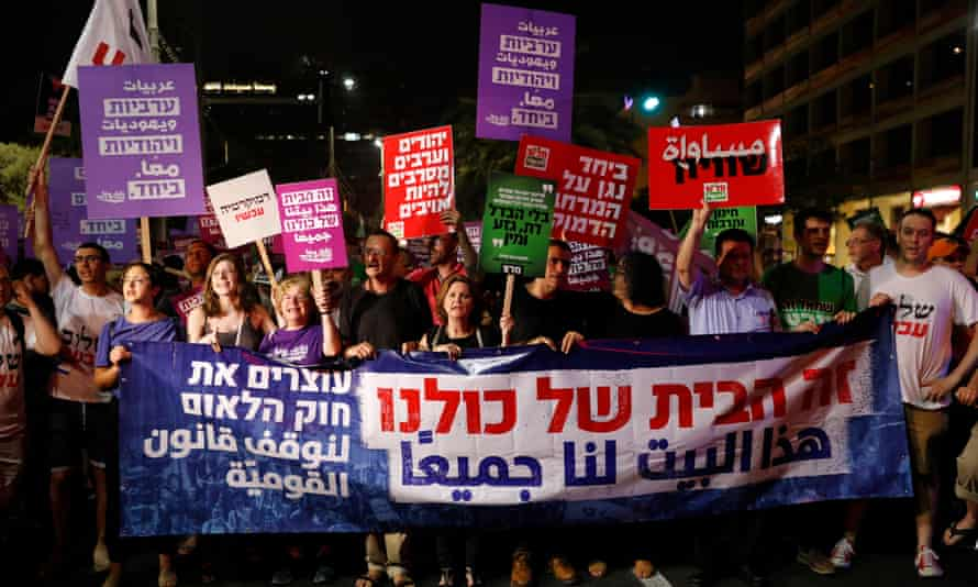 Israelis hold placards reading 'This house belongs to all of us' during a protest against the nation-state law in Tel Aviv, Israel on 14 July 2018