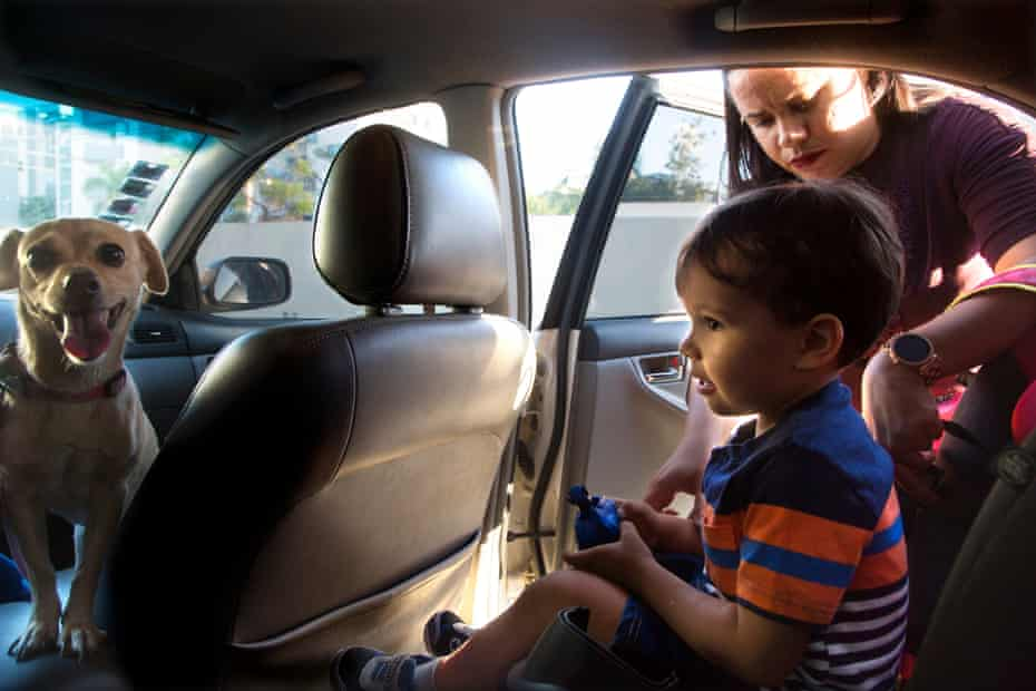 Noah, 3, is buckled into his carseat by his mother, Jennipher Mariel Gómez, 29, outside their home in Santiago, Dominican Republic